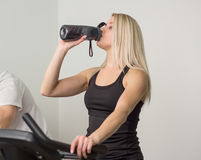 Woman drinks water on a stationary bike in the gym Royalty Free Stock Images
