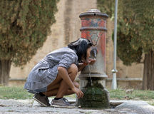 Woman drinks water on street. Woman drinks water from street pumps Royalty Free Stock Photos