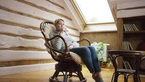 Woman drinks wine in a chair on attic. Woman drinks wine sitting in a chair on attic stock footage