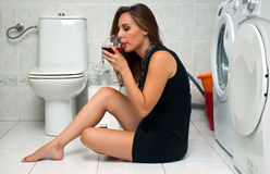 Woman drinks wine in her bathroom Stock Photography