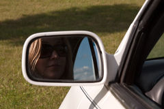 Woman Driver. Woman wearing sunglasses face in car rearview mirror royalty free stock photography