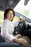 Woman driver. Asian woman driver sitting in car at steering wheel Royalty Free Stock Photos