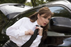 Woman driver adjusting her necktie in car mirror Stock Image