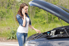 Woman driver calling for breakdown assistance. Beautiful young woman driver calling for breakdown assistance as she stands in front of her car with the bonnet up Royalty Free Stock Photos