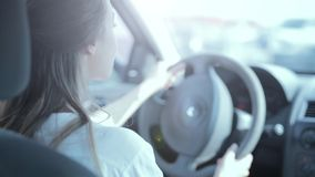 Woman driver in the car. Woman is sitting in the car while driving, waiting at the crossroads and looking at the road and around stock video
