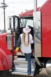 Woman driver entering the cab. A woman truck driver enters the cab of a big rig Stock Image