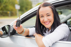 Woman driver leaning out the car window with keys Stock Photo