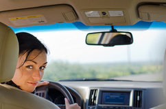 Woman driver looking into rear seat Royalty Free Stock Photography