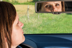 Woman driver looking in the rear-view mirror Stock Photo