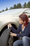 Woman driver measuring tyre profile Stock Photo