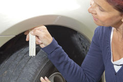 Woman driver measuring tyre profile Royalty Free Stock Image