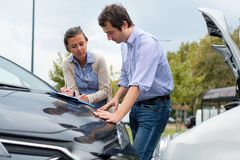 Woman driver and man reporting the damage of the car after accid. Woman driver and men filling insurance report document  after car accident Stock Photography
