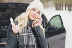 Woman driver near a black car, car problem, wintertime. Woman driver near a black car, car problem, soft focus background Royalty Free Stock Photo