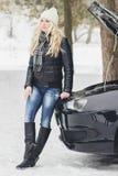 Woman driver near a black car, car problem, wintertime. Woman driver near a black car, car problem, soft focus background Stock Images
