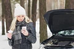Woman driver near a black car, car problem, wintertime. Woman driver near a black car, car problem, soft focus background Stock Image