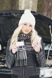 Woman driver near a black car, car problem, wintertime. Woman driver near a black car, car problem, soft focus background Royalty Free Stock Photography