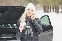 Woman driver near a black car, car problem, wintertime. Woman driver near a black car, car problem, soft focus background Stock Photo