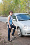 Woman a driver pumps full a wheel at a car Stock Photo