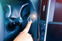 Woman driver pushing a start ignition button in the car. Woman driver pushing a start ignition button switch in the modern luxury car Royalty Free Stock Images