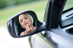 Woman driver putting lipstick Royalty Free Stock Image