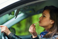 Woman driver putting on lipstick Royalty Free Stock Photo