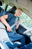 Woman driver putting safety belt Stock Photos