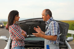 Woman driver and repairman in front of broken car Royalty Free Stock Photography