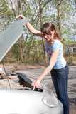 Woman a driver repairs a car Stock Photography