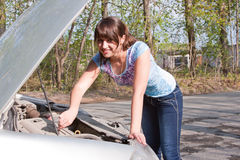 Woman a driver repairs a car Royalty Free Stock Image