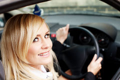Woman driver in right hand drive vehicle. Attractive blonde woman driver seated behind the wheel of a right hand drive vehicle looking out of her window with a Stock Images