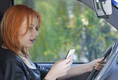 Woman driver sending sms on phone while driving Royalty Free Stock Image