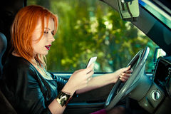 Woman driver sending text reading message on phone while driving. Concept of danger driving. Young woman driver red haired teenage girl texting on cell phone Stock Photos
