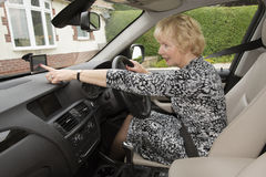Woman driver setting the satnav system in a car Royalty Free Stock Images
