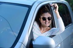 Woman driver showing keys. Woman driver showing the keys of her new car Stock Photo