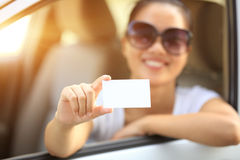 Woman driver sit in car hold blank business card Stock Photo