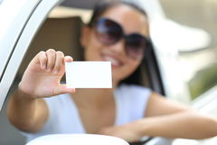 Woman driver sit in car hold blank business card Royalty Free Stock Images