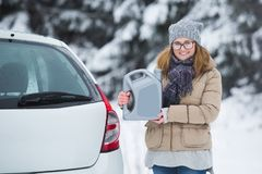 Woman driver standing next to car and holds the jerry can Stock Photo