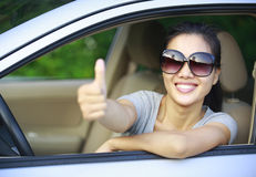 Woman driver thumb up. In car Stock Images
