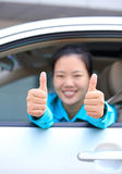 Woman driver thumb up in car Stock Photography