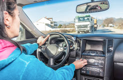 Woman driver tuning vehicle audio Stock Image