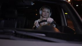 Woman driver wear headphones in car at night city. Slow motion, listening music stock video footage