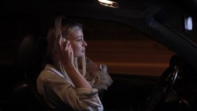 Woman driver wear headphones in car at night city. Slow motion, listening music stock video