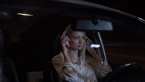 Woman driver wear headphones in car at night city. Slow motion, listening music stock footage