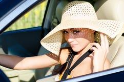 Woman driver wearing large straw sunhat stock photo