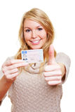Woman with drivers licence holding. Young happy woman with her new European drivers licence holding the thumbs up stock image