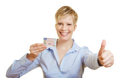 Woman with drivers licence holding thumbs up. Happy young woman with German drivers licence holding thumbs up (signature is faked royalty free stock photo