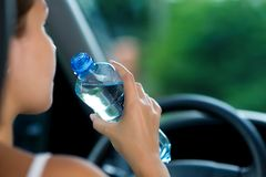 Woman drives a car and is going to drink water from a bottle