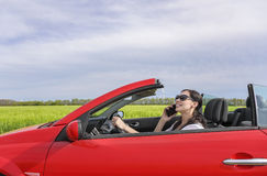 Woman drives the car and talking on the phone. Royalty Free Stock Photos