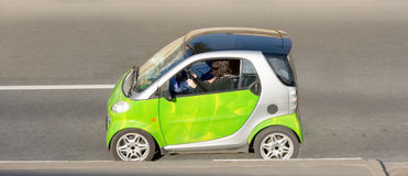 Woman drives clever smart mini. Green german car on road part of cars series Stock Photos
