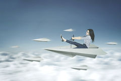 Woman drives a paper plane. Picture of a young businesswoman drives a paper plane on the sky Royalty Free Stock Photos